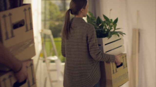 Couple carrying moving boxes into their new apartment