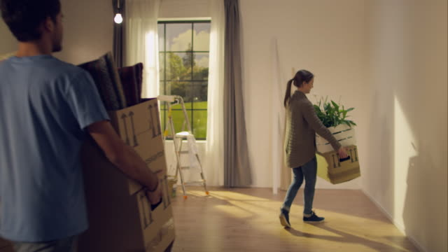 Couple carrying moving boxes into their new apartment video