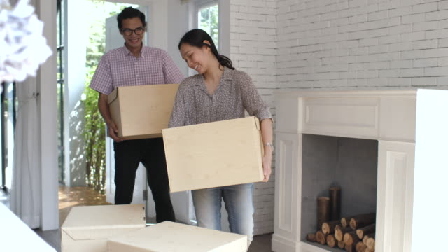 couple carrying moving boxes into their new home - new home stock videos & royalty-free footage