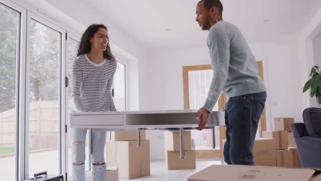 vídeos de stock e filmes b-roll de couple carrying table into new home on moving day - shot in slow motion - mesa mobília