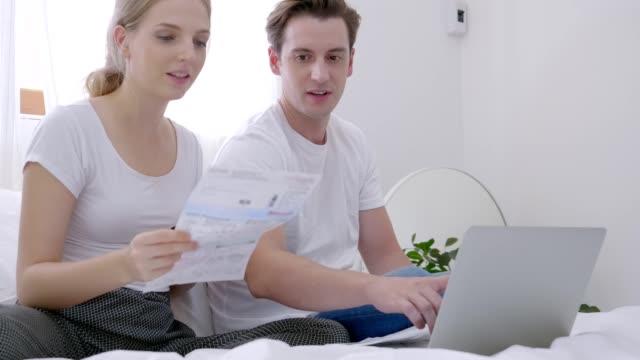 stockvideo's en b-roll-footage met paar kaukasische met behulp van het internet aangesloten op de laptop betalen de rekening met behulp van een creditcard toe te passen via de app, technologie geld portemonnee en online betaling concept - snavel