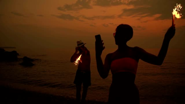 SLO MO Couple celebrating with sparklers on the beach video