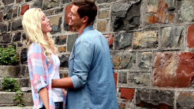 Couple chatting and embracing by brick wall video