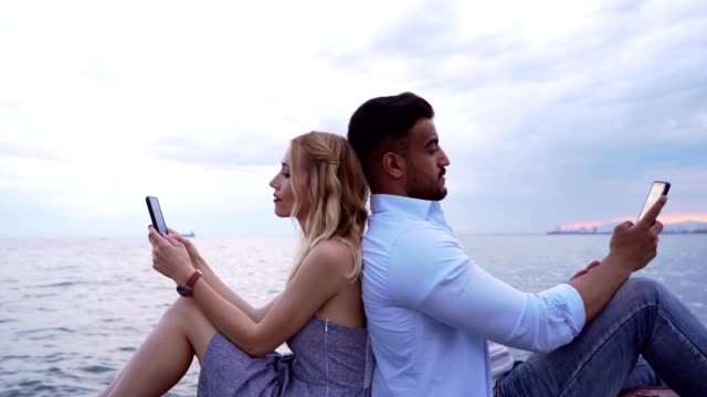 Couple chatting by the sea Smiling couple is sitting back to back by the sea and using smart phones. back to back stock videos & royalty-free footage
