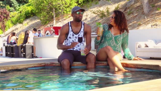 Couple Chatting on Edge of Water at Pool Party video