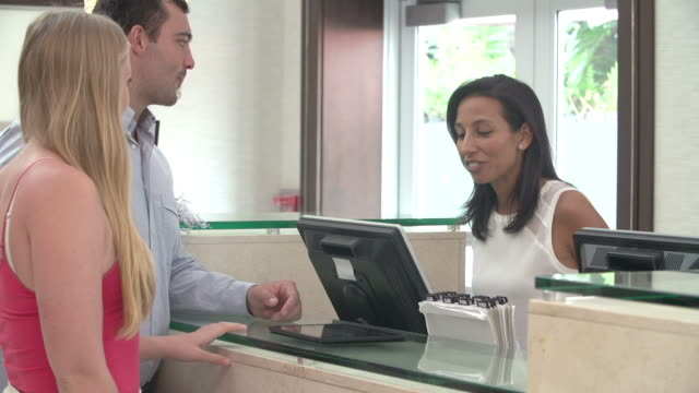 Paar beim Check-In an der Rezeption mit Tablet PC – Video