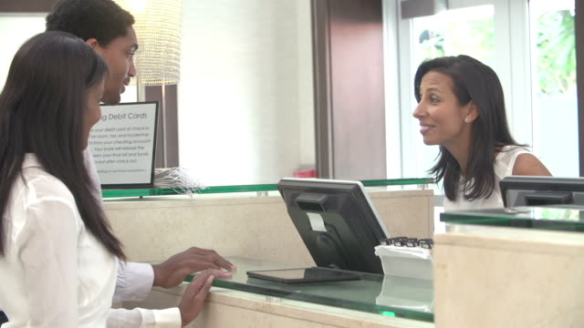 Couple Checking In At Hotel Reception Using Digital Tablet video
