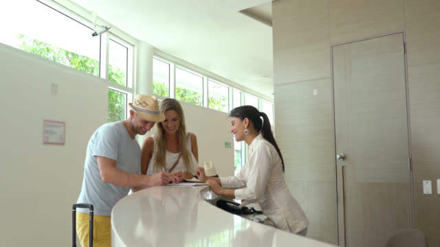 couple checking in to the hotel and receiving the card key - hotel checkin video stock e b–roll