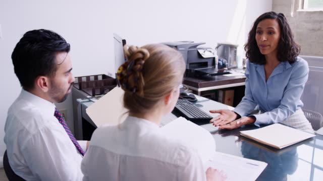 couple checking paperwork at a meeting with businesswoman - финансовый консультант стоковые видео и кадры b-roll