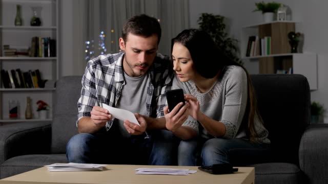 vidéos et rushes de couples vérifiant des reçus sur le téléphone à la maison - bec