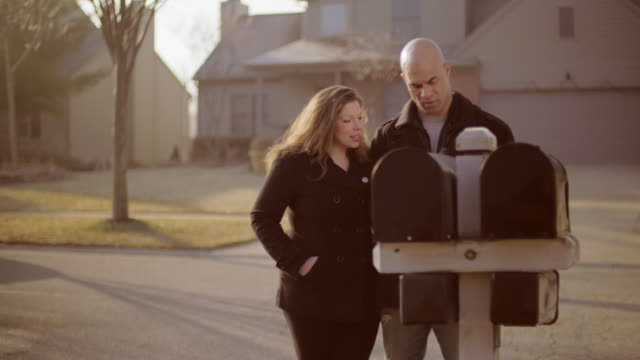 Couple checks mailboxes in early morning sunlight video
