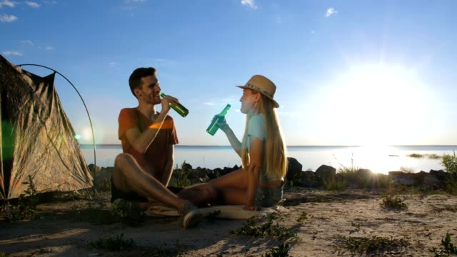 Couple cheering and drinking beer during camping