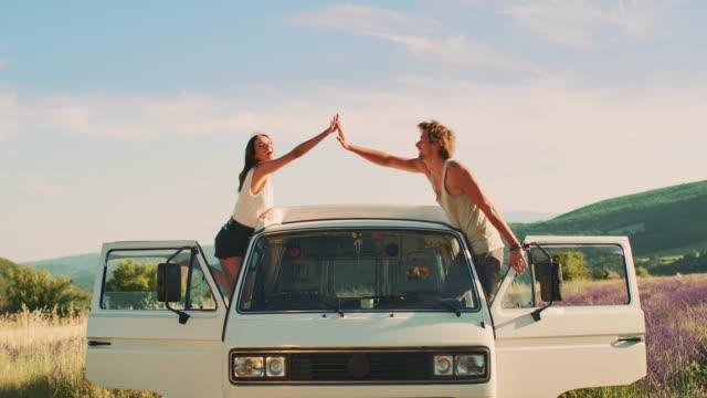 Couple cheering on van during road trip