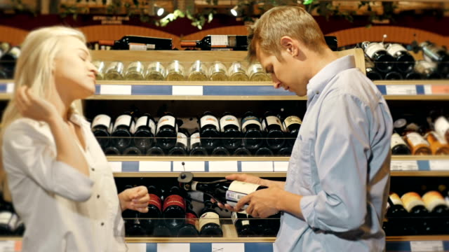 Couple Choose Wine Using Cellphone In Supermarket video