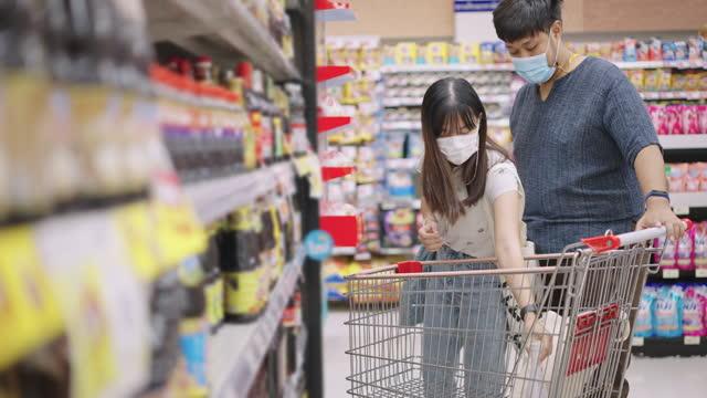 stockvideo's en b-roll-footage met paar dat flesgoederen in supermarkt kiest - aziatische etniciteit
