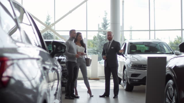 Couple Choosing New Car with Help of Salesman in Auto Showroom Caucasian family couple listening to salesman and discussing new cars in auto showroom car salesperson stock videos & royalty-free footage