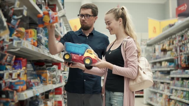 couple choosing toys for boys. - giocattolo video stock e b–roll