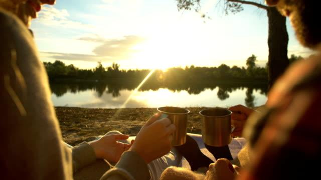 カップル カップを擦れる、野生の夜を過ごして、夕日、自然を見て - キャンプ点の映像素材/bロール