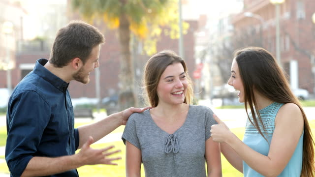 Couple congratulating a friend in the street