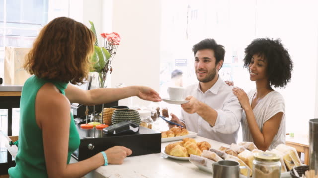 Couple contact less payment with smart phone at cafe - video