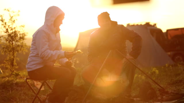 couple cooking dinner at the campfire at sunset. - camping stock videos & royalty-free footage