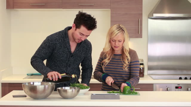 Couple cooking in kitchen looking at digital tablet video