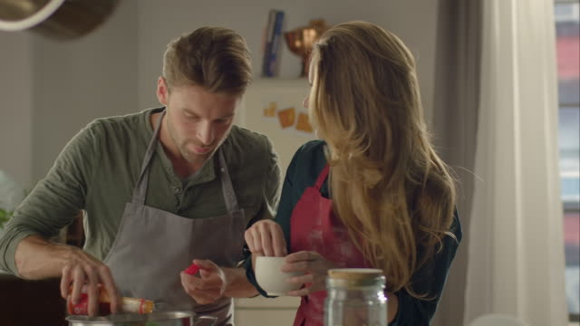 couple cooking together in kitchen and tasting food - laga mat bildbanksvideor och videomaterial från bakom kulisserna