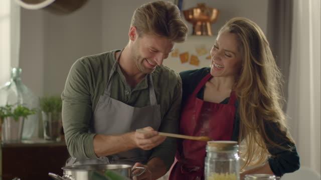 vídeos de stock e filmes b-roll de casal cozinhar juntos na cozinha, degustação de comida - avental