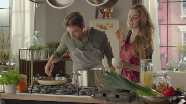 couple cooking together in kitchen - home cooking stock videos and b-roll footage