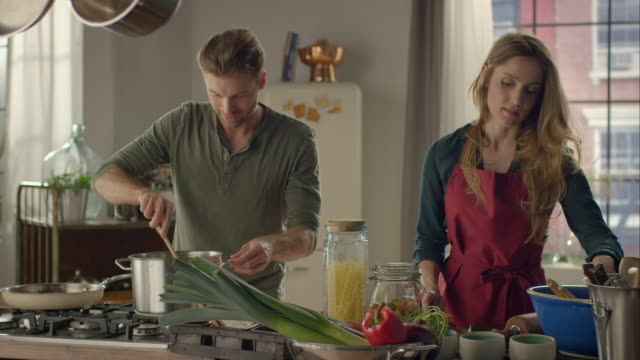 Couple cooking together in kitchen video