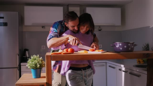Couple cutting tomato together in the kitchen and smiling