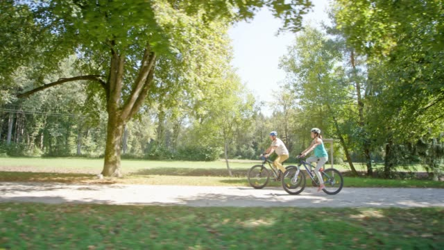 TS Couple cycling in the park through an avenue of trees in sunshine
