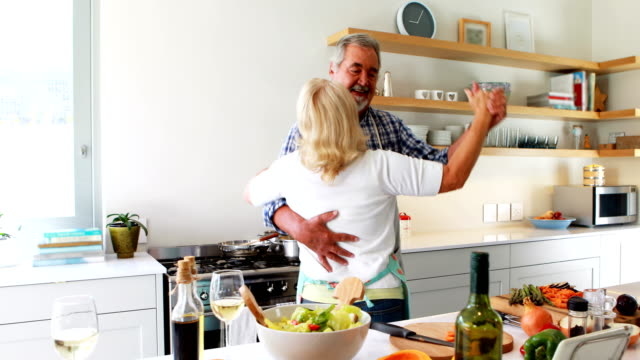 couple dancing in kitchen - coppia anziana video stock e b–roll