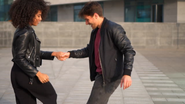 Couple dancing outdoors in city video