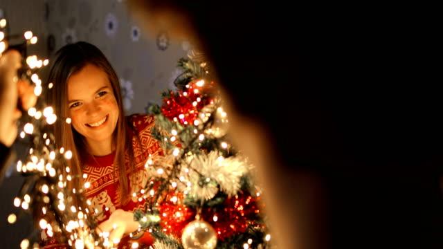 coppia che decora l'albero di natale. il periodo natalizio è ancora più divertente con te - decorare video stock e b–roll