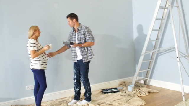 Couple Decorating Nursery For Arrival Of New Baby Couple painting nursery ready for arrival of new baby - man touches pregnant wife's stomach. Shot on Sony FS700 at a frame rate of 25fps painting activity stock videos & royalty-free footage