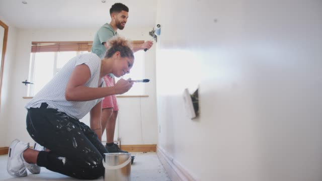 Couple Decorating Room In New Home Painting Wall Together Young couple decorating new home painting wall with brush and paint roller - shot in slow motion renovation stock videos & royalty-free footage