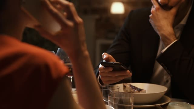 Couple dining together and ignoring each other Couple dining together at the restaurant and ignoring each other, the woman is having a phone call and the man is messaging with his smartphone ignoring stock videos & royalty-free footage