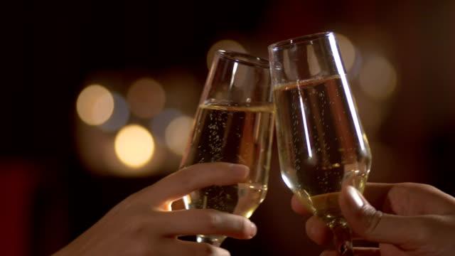 vidéos et rushes de couples dinning et toasting -détail tiré. a l'intérieur, restaurant, dîner romantique. 4k (4k) - champagne