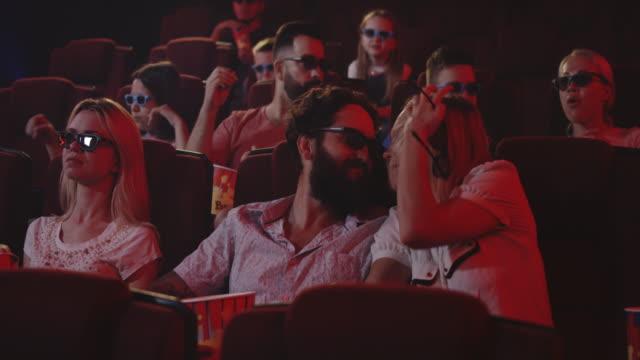 couple disturbing cinema audience with talking - kids kiss embarrassed video stock e b–roll