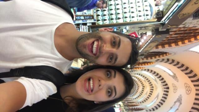 couple doing a video chat at bazaar market in istanbul, turkey - вертикальный стоковые видео и кадры b-roll