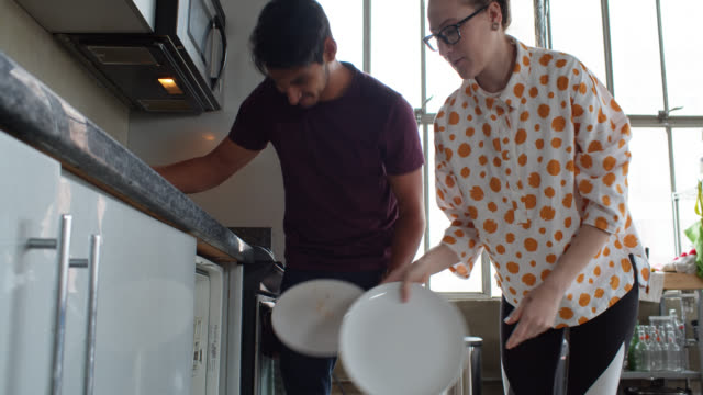 Couple Doing Chores at Home A young heterosexual couple at home together in their urban loft apartment, loading the dishwasher and cleaning up after a meal. The woman is pregnant. loft apartment stock videos & royalty-free footage