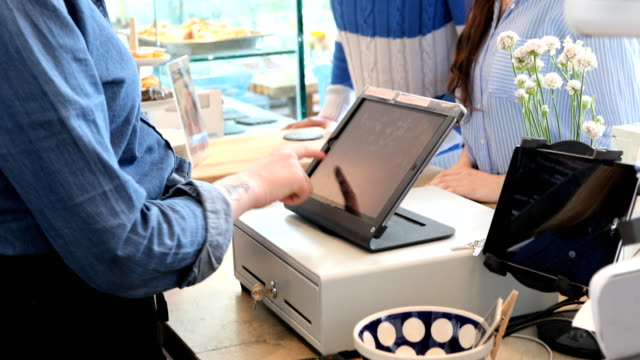 Couple Doing Contactless Payment To Female Barista Handheld shot of female barista using cash register at cafe. Midsection of man is standing with woman doing contactless payment. They are at checkout counter. register stock videos & royalty-free footage