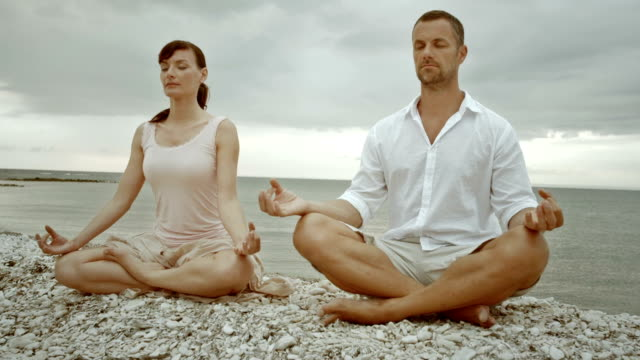 TU Couple doing half lotus yoga pose by the sea Tilt up medium shot of a couple, a man and a woman, doing half lotus or ardha padmasana yoga pose while sitting on the white pebbles and surrounded by the sea. lotus position stock videos & royalty-free footage