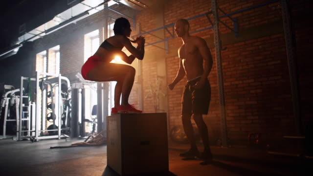 vídeos de stock e filmes b-roll de couple doing jump box at fitness club - agachar se
