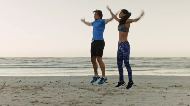 Couple doing jumping jacks on beach intense workout Fit active lifestyle couple doing vigorous exercise jumping jacks by the ocean, body work out warm up at sunrise leaning stock videos & royalty-free footage
