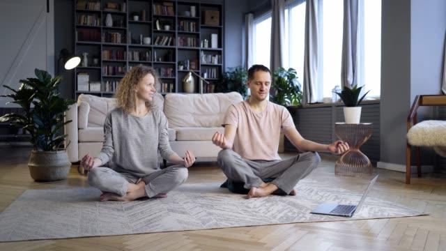 vídeos de stock e filmes b-roll de couple doing morning exercise in home interior - treino em casa