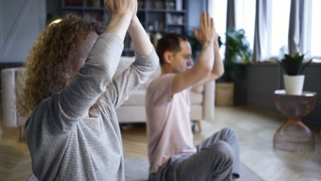 Couple doing morning exercise in home interior Happy couple in pajamas doing morning practice in modern living room. Close-up portrait woman and man sitting in lotus pose rising folded hands, meditates before laptop while watching yoga lessons yoga stock videos & royalty-free footage