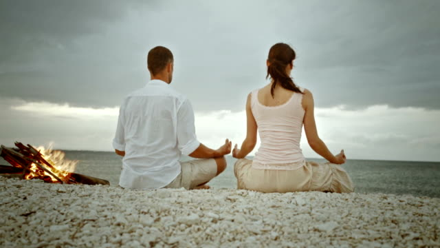 PAN Couple doing yoga on the beach video