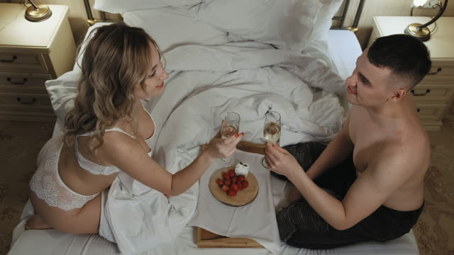 couple drink champagne in a bed